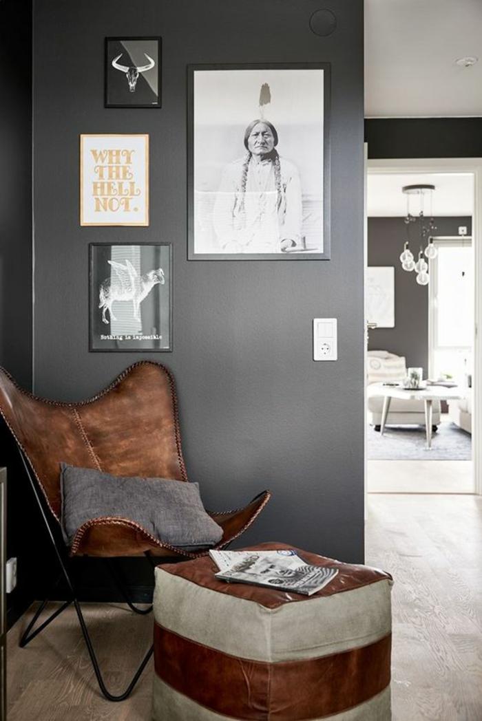 quelle couleur pour un couloir gris anthracite, fauteuil en cuir marron et tabouret en cuir marron et gris, mur en gris avec des photos en cadres noirs, sol recouvert de parquet lisse en PVC