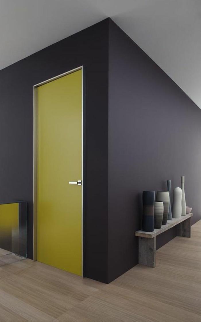 peinture bleu canard sur le mur et porte jaune, parquet lisse en couleur beige, meuble pour poser des vases et des pots décoratifs, espace minimaliste