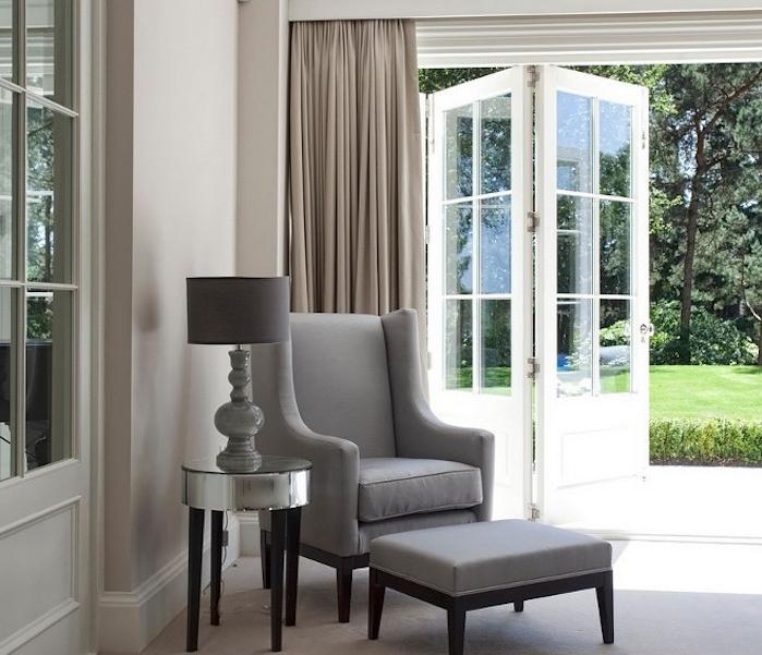 exemple de gris souris peinture couleur claire, rideaux gris de beige, fauteuil et tabouret gris, lampe grise sur une table d appoint design, ouverture sur jardin