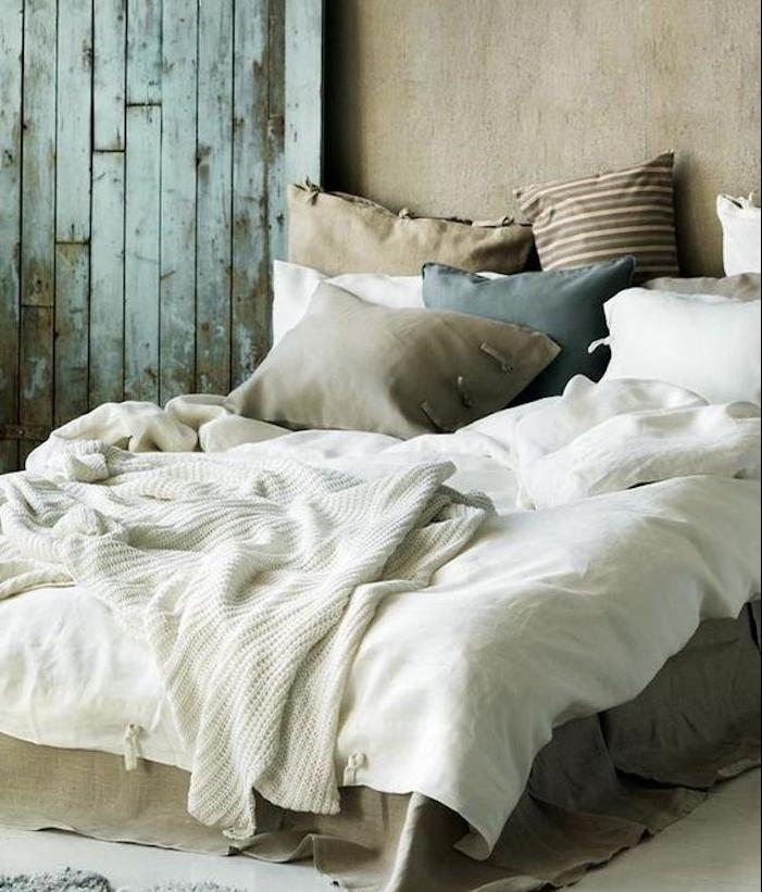 gris souris peinture sur les murs d une chambre à coucher en gris et blanc, plaid blanc tricot, coussins grege, bleu et marron, porte usée
