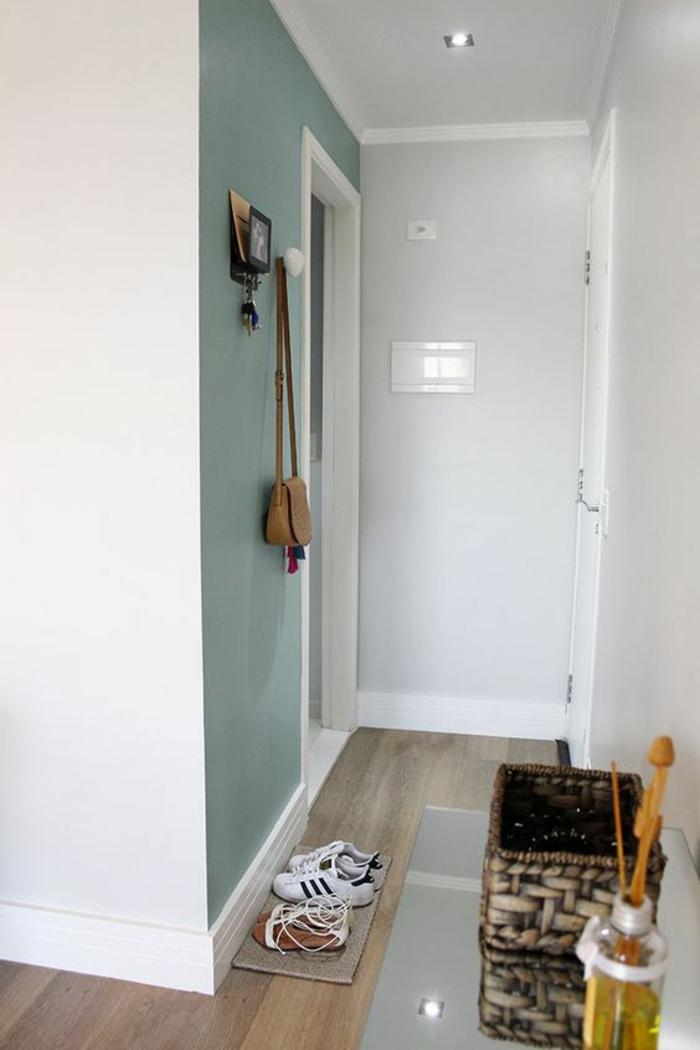 decoration couloir long et etroit avec mur en vert menthe, murs en blanc, parquet en PVC nuances marron clair et marron foncé, patère en forme de boule blanche
