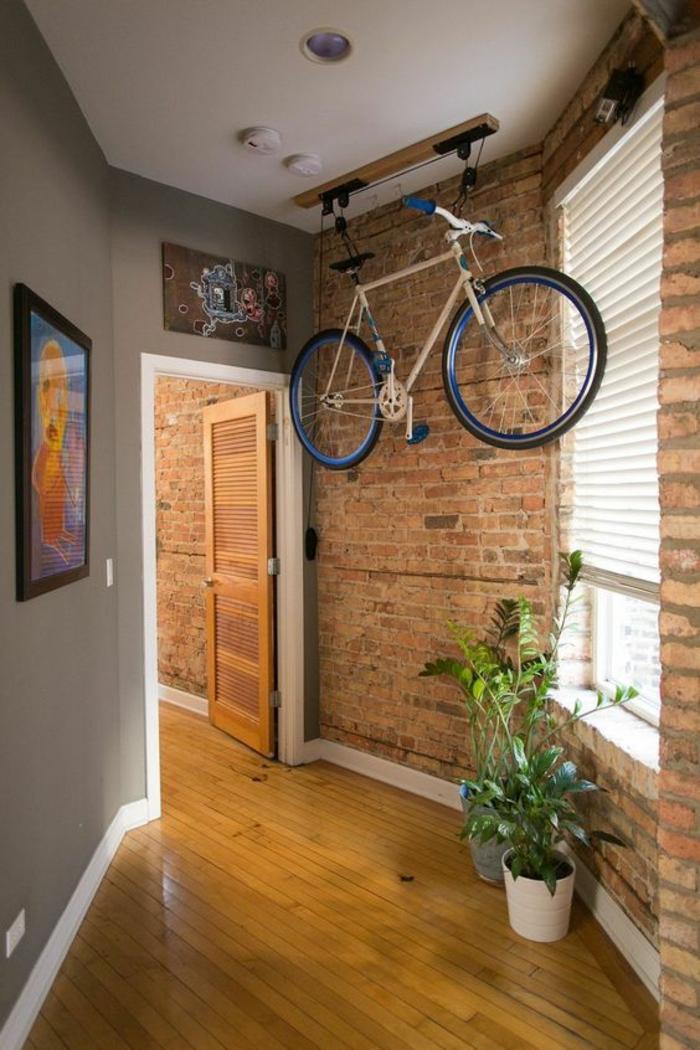 quelle couleur pour un couloir, murs en briques marron foncé, murs en gris clair, parquet dans les nuances du jaune, deux grands pots blancs avec des grandes plantes vertes, vélo bleu suspendu au plafond et fixé avec système à poulies