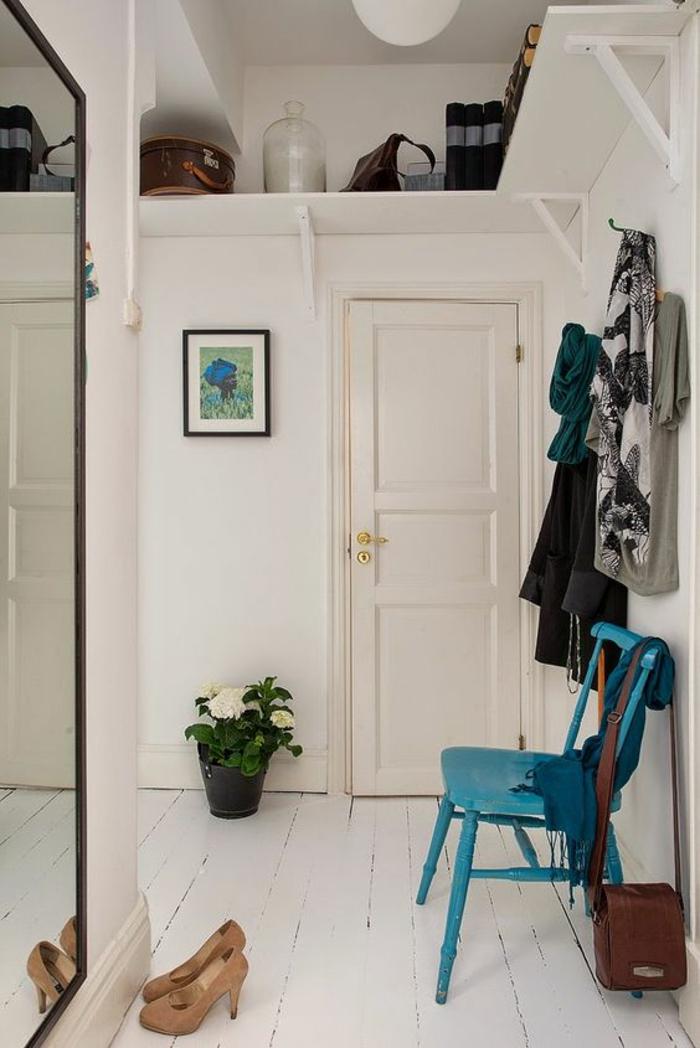 deco couloir avec grand miroir rectangulaire au cadre noir, chaise en bois peinte en turquoise, sol recouvert de bois peint en blanc, pot noir avec plante fleurie en fleurs blanches