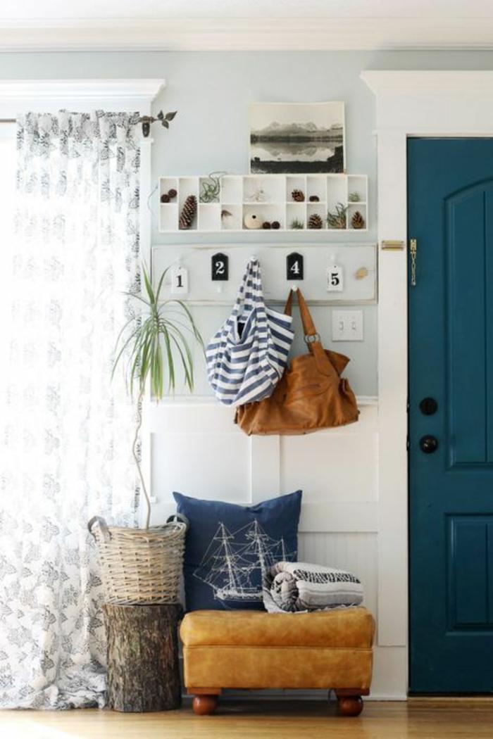 comment decorer un couloir, porte en bleu canard, rideaux avec des motifs floraux en bleu et blanc, tabouret bas et carré en faux cuir couleur caramel, parquet en bois PVC en couleur caramel