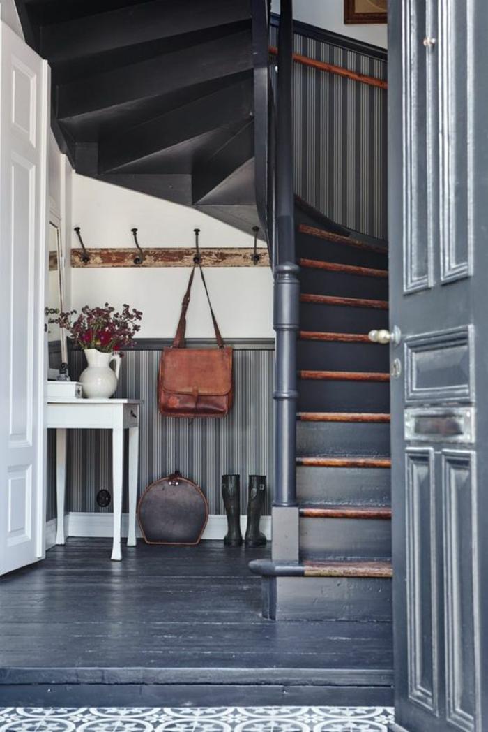 quelle couleur pour un couloir peinture bleu canard sur le sol en bois, sur la porte et sur les escaliers, porte blanche, table blanche, carrelage en blanc et bleu pastel, patère vintage en bois brut et en métal noir, fleurs rouges dans un pot blanc