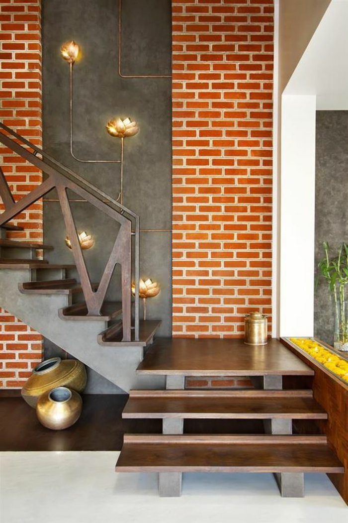 idée entrée mur en briques oranges et escalier avec des marches en métal couleur bronze, éléments déco avec des fleurs en métal bronze