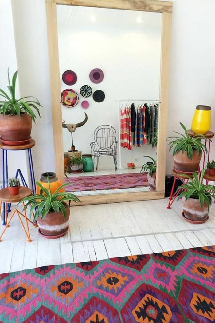 comment decorer un couloir avec un grand miroir posé au sol avec cadre de bois clair, tapis coloré avec des motifs graphiques, pots colorés en jaune et orange avec des fleurs, plats en paille tressée colorés suspendus sur le mur blanc, quatre porte-plantes en métal coloré en rouge et bleu électrique, fauteuil de jardin en métal noir