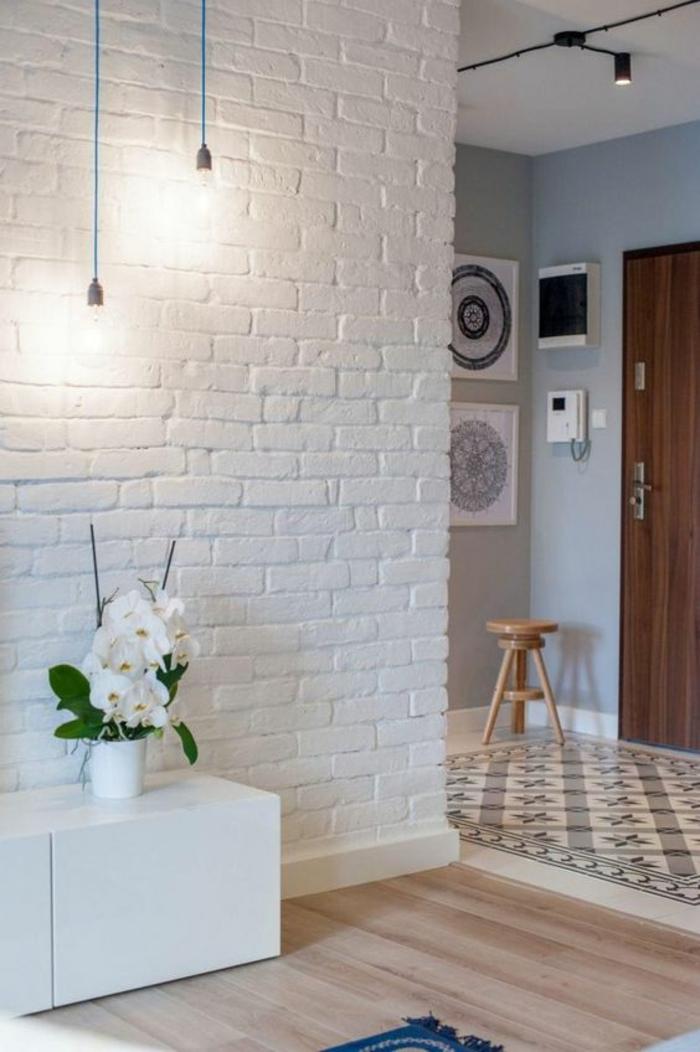 quelle couleur pour un couloir, mur en briques blanches, deux luminaires longs suspendus avec deux ampoules nues rétro, combinaison de carrelage avec des fleurs en rose et gris et parquet en bois PVC