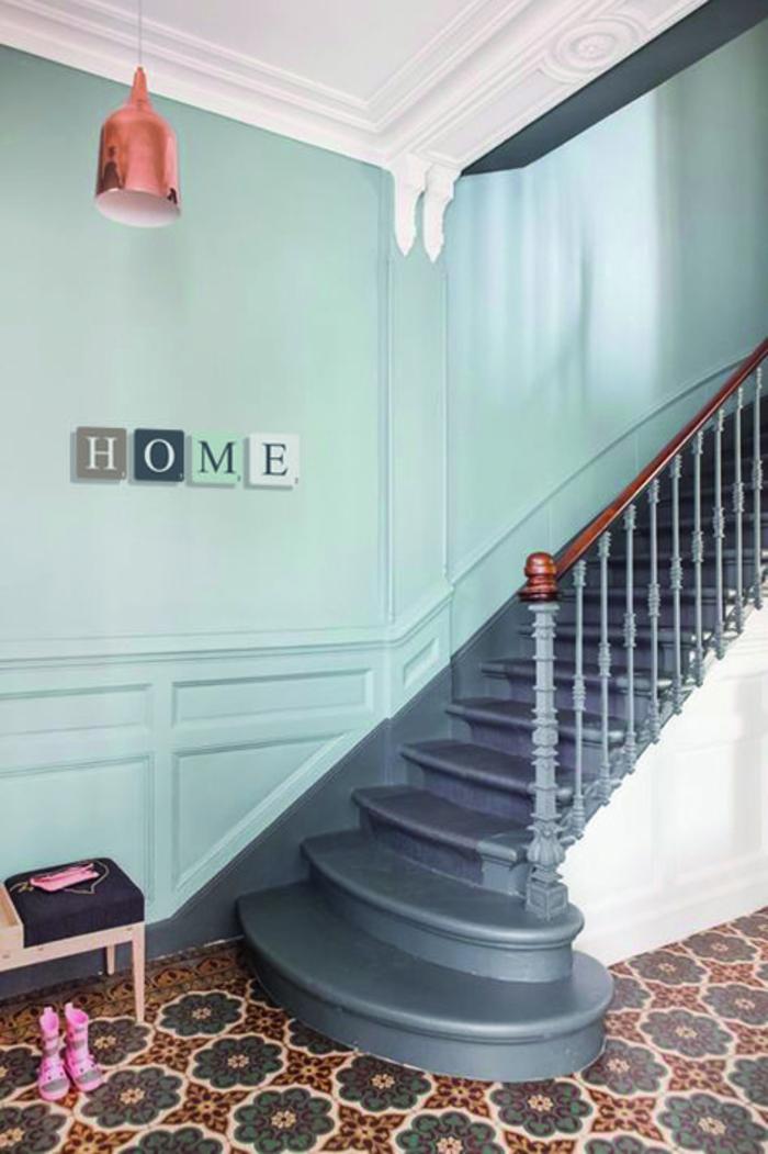 peinture bleu canard et vert menthe, plafond blanc avec des frises, lampadaire en couleur bronze imitation du métal, carrelage en motifs floraux en vert, rouge et jaune, escalier en bleu canard, banc rose, panneau décoratif sur le mur de l'escalier en forme de quatre lettres en couleurs différentes HOME