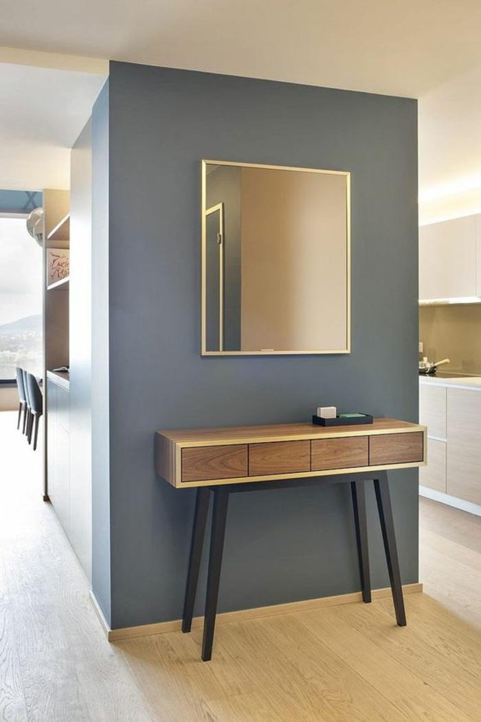 peinture bleu canard sur un mur, parquet en PVC beige imitation bois, meubles beiges, meuble d'entrée table en marron et beige avec des pieds en gris anthracite