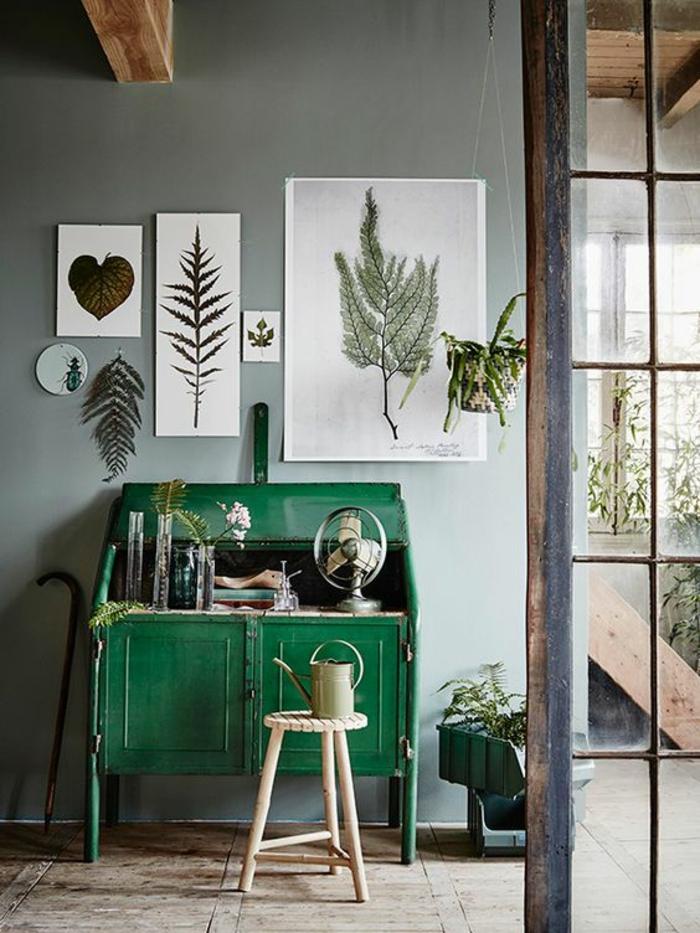 comment decorer un couloir avec meuble vintage peint en vert vif, tabouret en bois clair en forme ronde, cinq photos d'herbes et de plantes au mur, peint en gris, parquet en bois clair, des poutres en bois rude au plafond, style maison de campagne