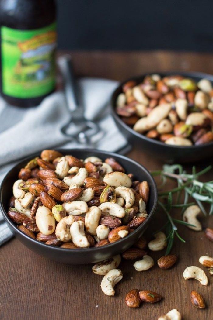 idée pour un apéritif dinatoire simple entre amis, un mélange délicieux de noix épicées servies dans une coupelle pour accompagner un plateau de fromages