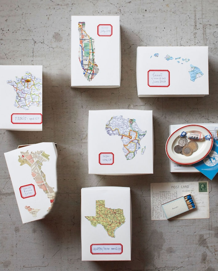 cadeau anniversaire femme, des boites en papier blanches décorés de cartes des continents pour recueillir des souvenirs de voyages