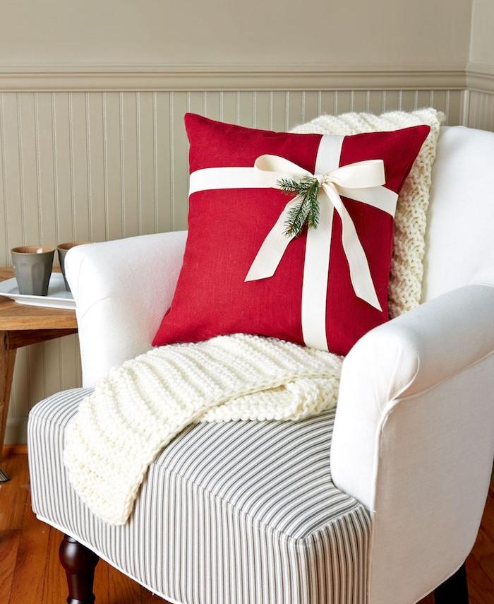 exemple d idée cadeau femme 50 ans, un coussin rouge décoré de ruban blanc et branche de pin, plaid blanc, cadeau de noel pour femme