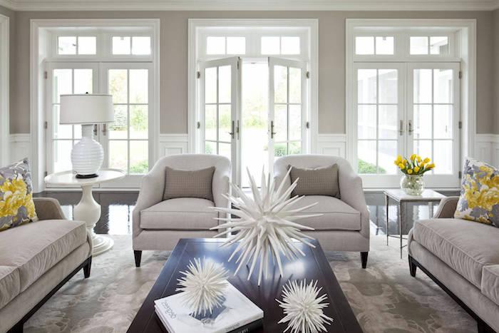canapés, fauteuils et mur gris clair, nuance taupe dans un salon en gris et blanc avec des accents jaunes, table basse bois marron