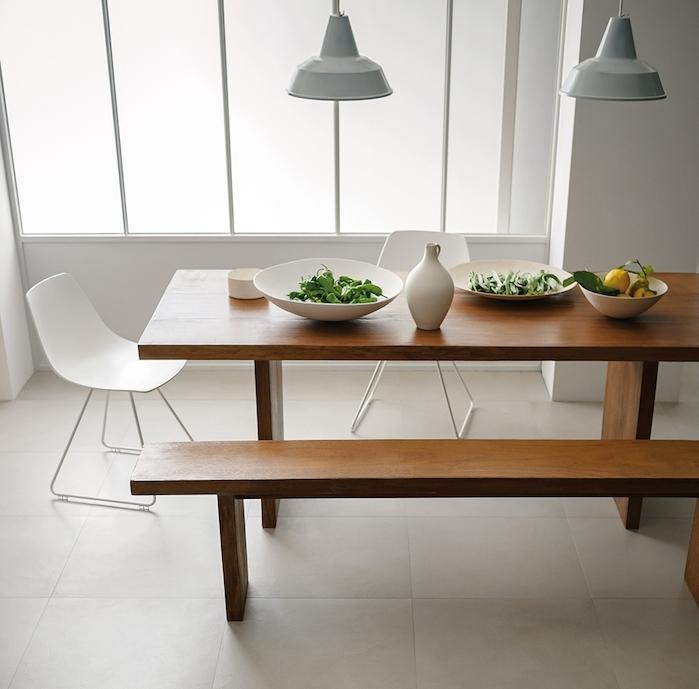 salle à manger carrelage sol couleur grege, table et banc en bois massif, chaises scandinaves blanches, suspensions gris clair, murs blancs
