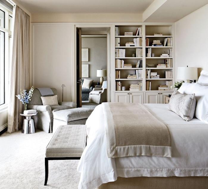 exemple d amenagement chambre à coucher couleur taupe clair, linge de lit gris et blanc, fauteuil et tabouret gris, bibliothèque encastrée dans un mur