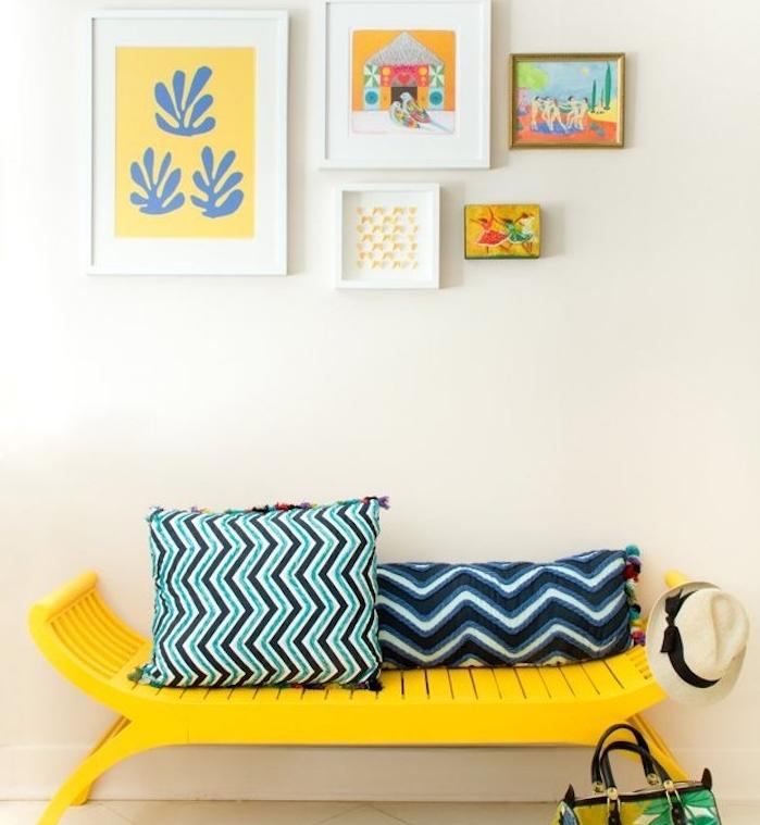 comment peindre un meuble en jaune, un banc customisé et coussins bleu et noir à motifs géométriques, deco de cadres sur le mur
