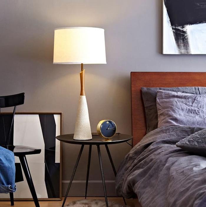 mur taupe couleur et linge de lit gris anthracite dans une chambre à coucher, parquet clair, cadre décoratif en noir et blanc, table de nuit noire