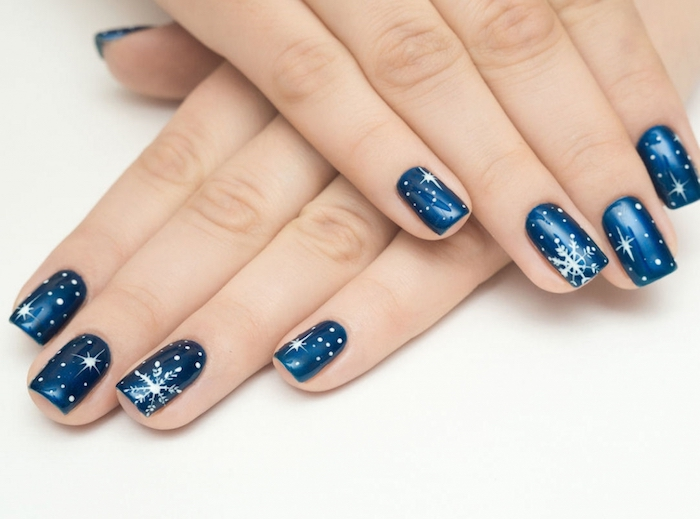 deco ongle noel en venis à ongles couleur bleu foncé et motif flacon de neige et étoiles, idée simple