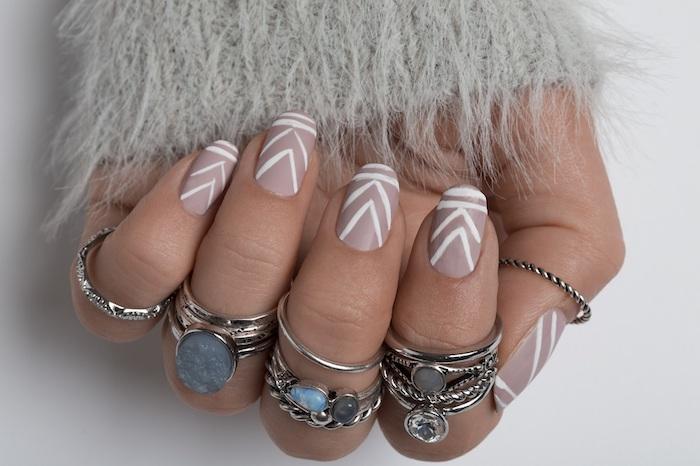 deco ongle noel à vernis couleur nude et lignes blanches, plusieur bagues et accessoires, pull gris