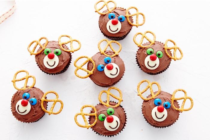 petits gateaux de noel, recette de cupcake au chocolat avec glaçage crème cacao, décors museau et des yeux sucrés et bois en bretzels, motif rudolphe le renne