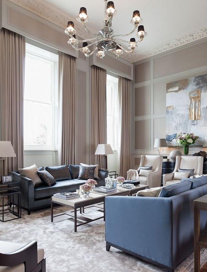murs et rideaux couleur gris taupe, canapés bleus, tapis gris, fauteuils grege, tables basses en bois, lustre exubérant