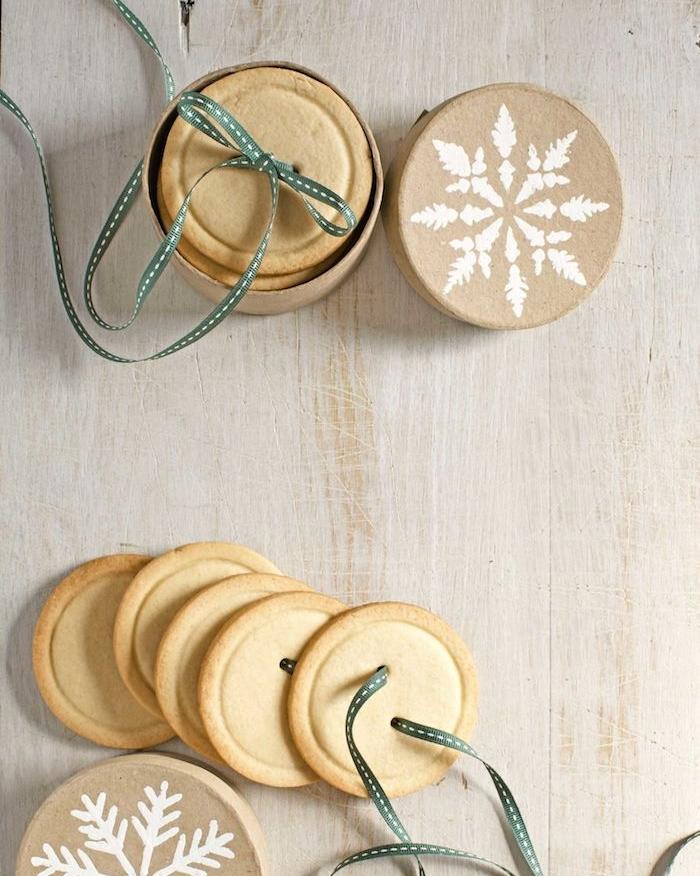 sables de noel en forme de boutons avec un ruban décoratif dans une boîte à cadeau en carton, dessert simple et rapide, idée de cadeau gourmand