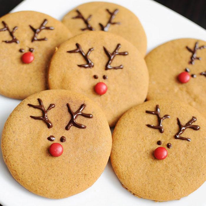 recette sablé de noel facile, biscuits en pain d épices ronds avec bois au chocolat et nez en bonbons rouge