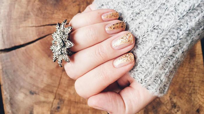 verni a ongle noel couleur or de paillettes pour réaliser un motif sapin, pull gris, bague argenté
