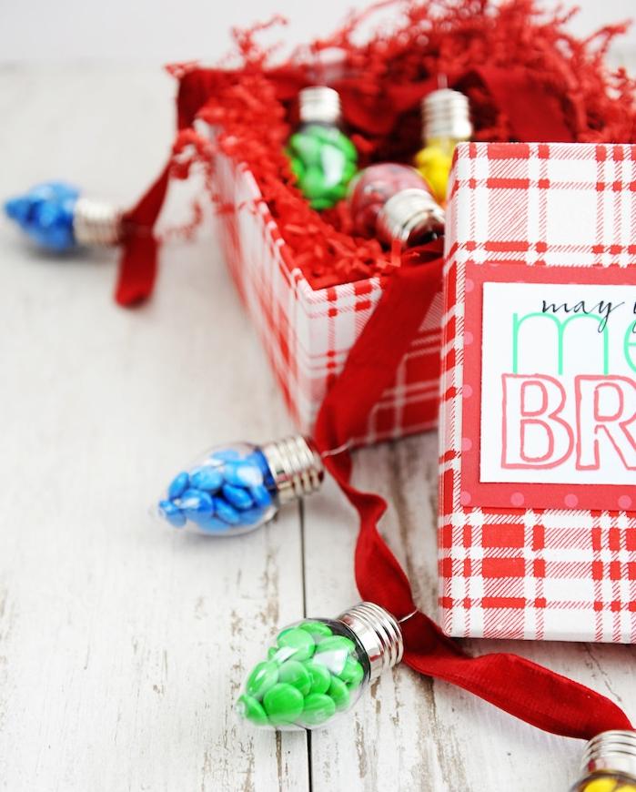 cadeau femme noel, idée gourmande, guirlande lumineuse en ampoules remplies de bonbons colorés mm enfilés sur un ruban rouge