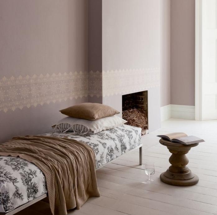 peinture taupe claire dans un salon épuré avec cheminée, chaise longue revêtement blanc à motifs gris, couverture et coussins marron de gris, tabouret en bois