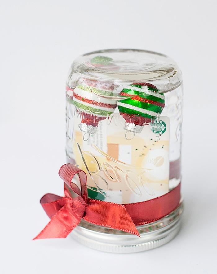 idee cadeau noel ado 15 ans, une boule à neige en verre dans un bocal décoré de ruban rouge et boules de noel à l intérieur