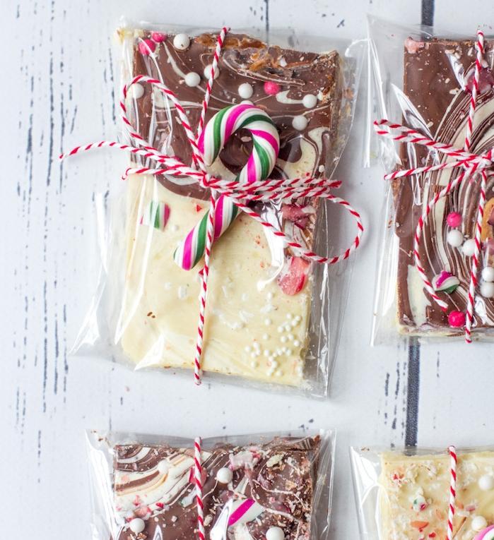 cadeau de noel pour femme, un sache en plastique transparent avec du chocolat au lait et chocolat blanc, décoration de ficelle rouge et blanc et canne de bonbon