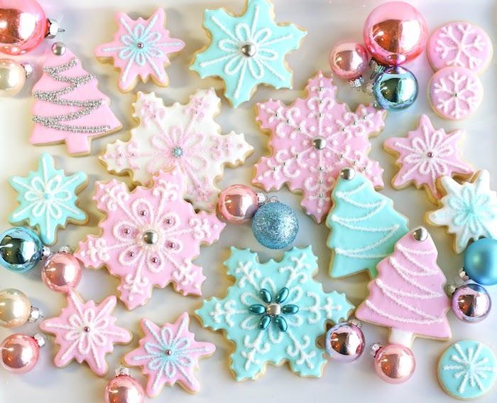 biscuit de noel recette, biscuits en forme de flacon de neige et arbres de nel, comment faire un glacage, couleur rose, blanche et bleue, deco boules de noel