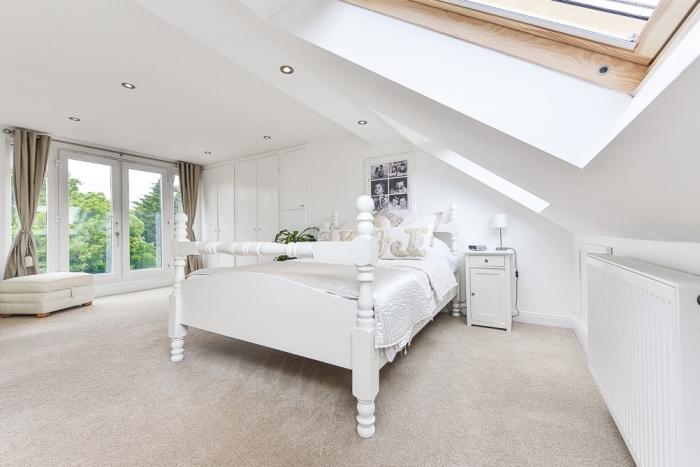 chambre a coucher au grenier avec grandes fenêtres et meubles en bois peints en blanc de style moderne