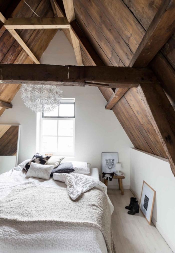 ambiance cozy dans une chambre à coucher sous pente avec grand lit bas décoré de plaids doux et coussins
