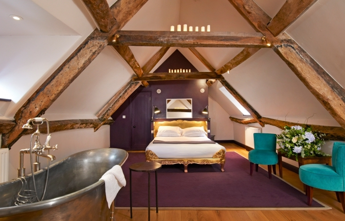 aménagement moderne du grenier avec fauteuil turquoise tapis violet et cadre de lit doré, baignoire dans la chambre à coucher sous combles