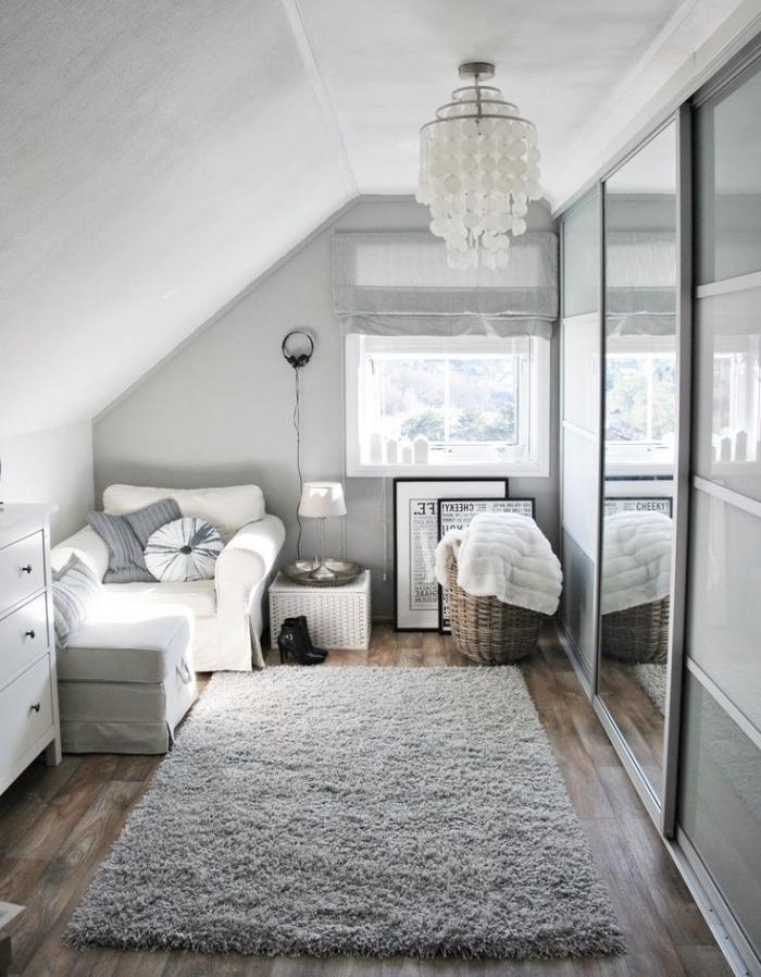 décoration cozy en style scandinave dans une petite chambre au grenier avec tapis moelleux et fauteuil convertible