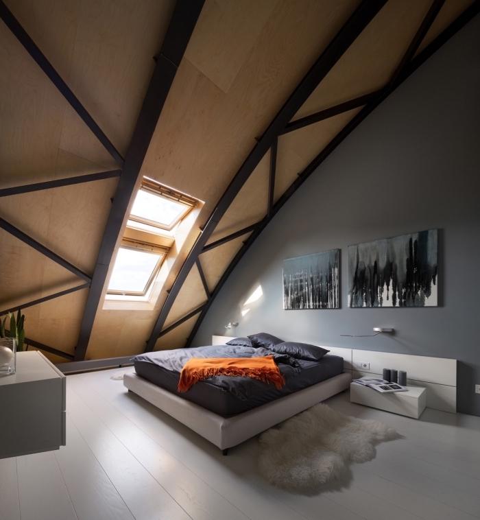 chambre a coucher au grenier avec murs en gris et plafond en bois et noir, cadre de lit blanc et meubles sans poignées