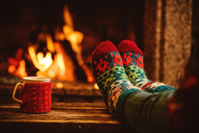 idee deco cocooning hiver, cheminée romantique, chaussettes vert et rouge, tasse de cadé, décor en bois, style hygge hiver