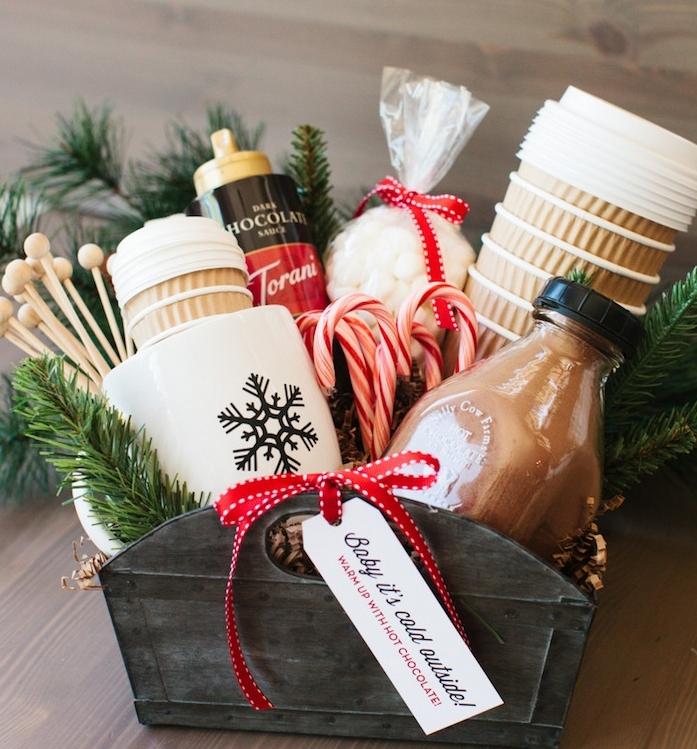 kit panier produits pour chocolat chaud avec des gobelets, cacao, guimauves, branches de pin tasse à café blanche avec un flacon de neige noir, idée cadeau noel femme
