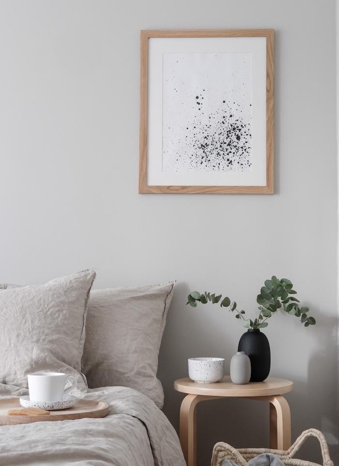 exemple de chambre à coucher gris et bois, taupe couleur linge de lit, table de nuit en bois, plante verte, cadre bois avec art, feuille blanches tachetée