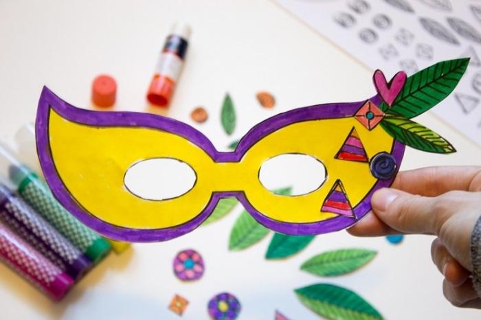 idée activité manuelle, modèle de masque multicolore en papier avec petites coupures de papier sous la forme de feuilles et coeurs