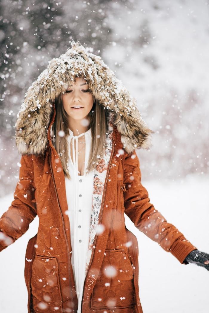 tunique femme, modèle de manteau long en marron avec capuche en faux fur beige et gants noirs