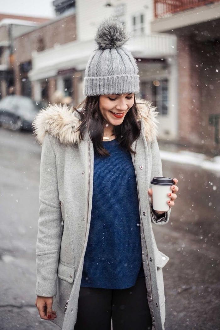 tenue hiver, associer le pull bleu foncé avec pantalon noir et manteau long en gris avec capuche en faux fur beige