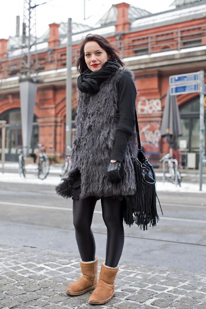 femme bien habillée, manteau en faux fur gris sans manches avec veste noir, écharpe longue portée avec bottines marron