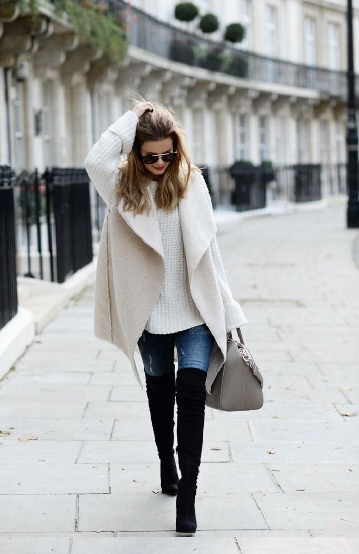 idee pour s habiller, porter le pull blanc loose avec manteau beige paire de jeans clairs et bottes cuissardes noires