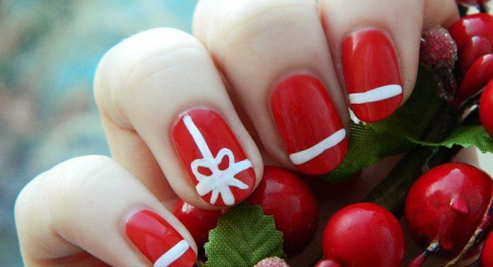 nail art noel facile, un vernis à ongles rouge avec motif lignes blanches et neud de ruban blanc, houx rouge