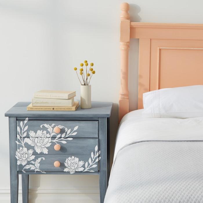 peindre un meuble en bois, idée de table de nuit repeinte en gris et motifs floraux blancs décorés au pochoir, linge de lit blanc